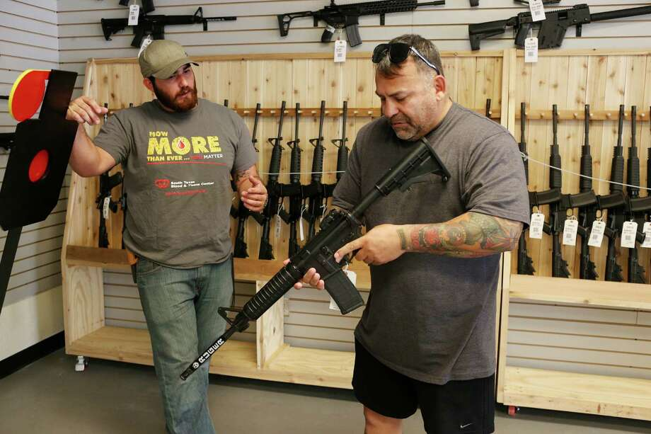 Zeke Hernandez (left) helps out customer Ifrain Zavala as he takes a look at an AR-15 at Adelbridge & Co. Photo: Photos By Jerry Lara / San Antonio Express-News / © 2016 San Antonio Express-News