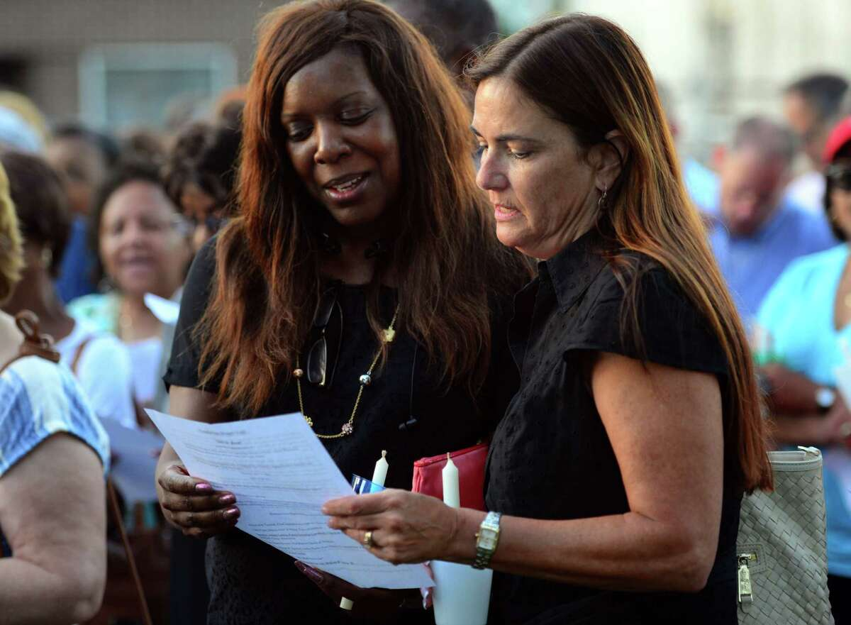 Pertrinea Cash, of Trumbull, left, and April Obermeyer, of Fairfield, sing together during a short service before a candlelight vigil held at the First Baptist Church of Stratford on Stratford Avenue in Stratford, Conn. on Thursday July 14, 2016. The vigil was held in response to the violent attacks against citizens and police last week. The vigil was a collaboration between the First Baptist Church of Stratford, First Church Congregational in Fairfield and the Stratford Interfaith Clergy Association.