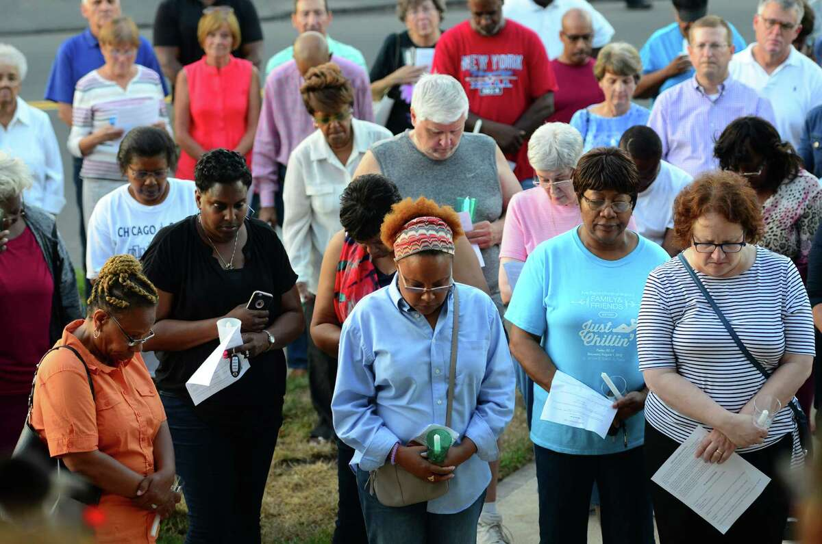 People bow their heads in prayer during a short service before a candlelight vigil held at the First Baptist Church of Stratford on Stratford Avenue in Stratford, Conn. on Thursday July 14, 2016. The vigil was held in response to the violent attacks against citizens and police last week. The vigil was a collaboration between the First Baptist Church of Stratford, First Church Congregational in Fairfield and the Stratford Interfaith Clergy Association.