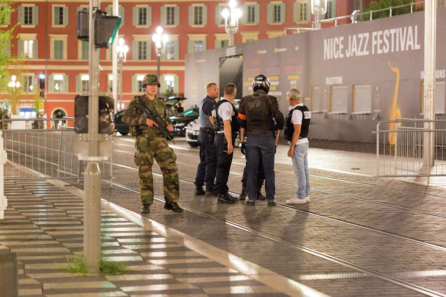 "Police officers and a soldier stand by the sealed off area of an attack after a truck drove on to the sidewalk and plowed through a crowd of revelers who'd gathered to watch the fireworks in the French resort city of Nice, southern France, Friday, July 15, 2016. A spokesman for France's Interior Ministry says there are likely to be ""several dozen dead"" after a truck drove into a crowd of revelers celebrating Bastille Day in the French city of Nice. (AP Photo/Ciaran Fahey) Photo: Ciaran Fahey, STF / AP"
