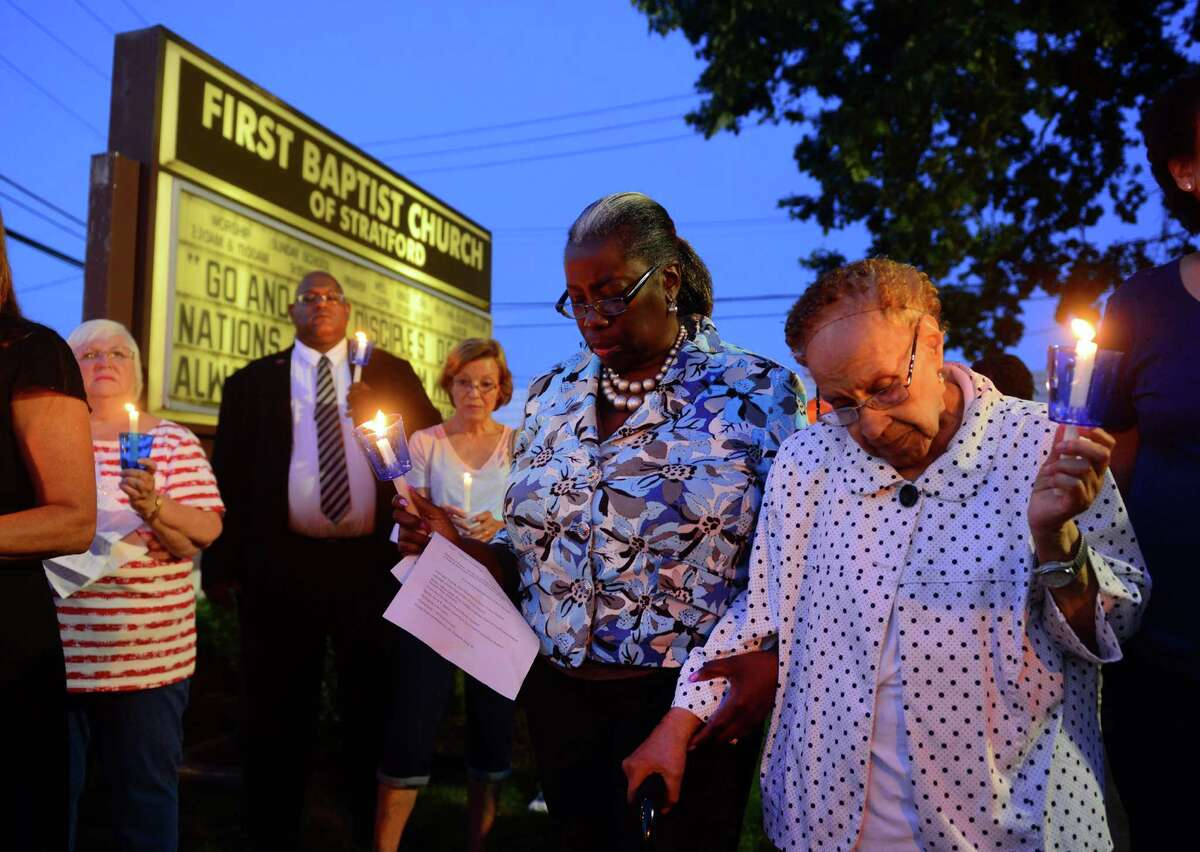 Sheila Mayers-Osorio and her mother Mary Williams, right, bow their heads in prayer at the conclusion of a candlelight vigil held at the First Baptist Church of Stratford on Stratford Avenue in Stratford, Conn. on Thursday July 14, 2016. The vigil was held in response to the violent attacks against citizens and police last week. The vigil was a collaboration between the First Baptist Church of Stratford, First Church Congregational in Fairfield and the Stratford Interfaith Clergy Association.