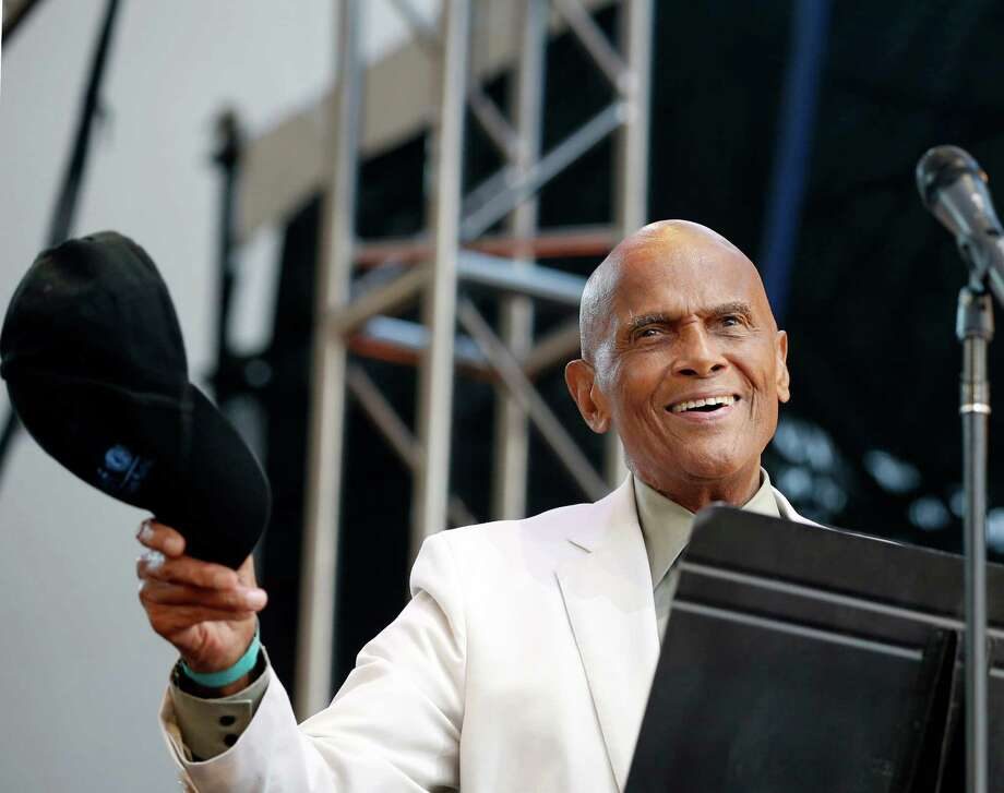 Singer and activist Harry Belafonte tips his cap to the crowd before speaking during a memorial tribute concert for folk icon and civil rights activist Pete Seeger at Lincoln Center's Damrosch Park in New York, Sunday, July 20, 2014. Seeger died at age 94 in January. (AP Photo/Kathy Willens) ORG XMIT: NYKW111 Photo: Kathy Willens / AP