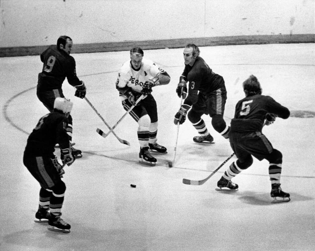 1974 - Houston Aeros Gordie Howe is surrounded by Vancouver Blazers as he  goes for the