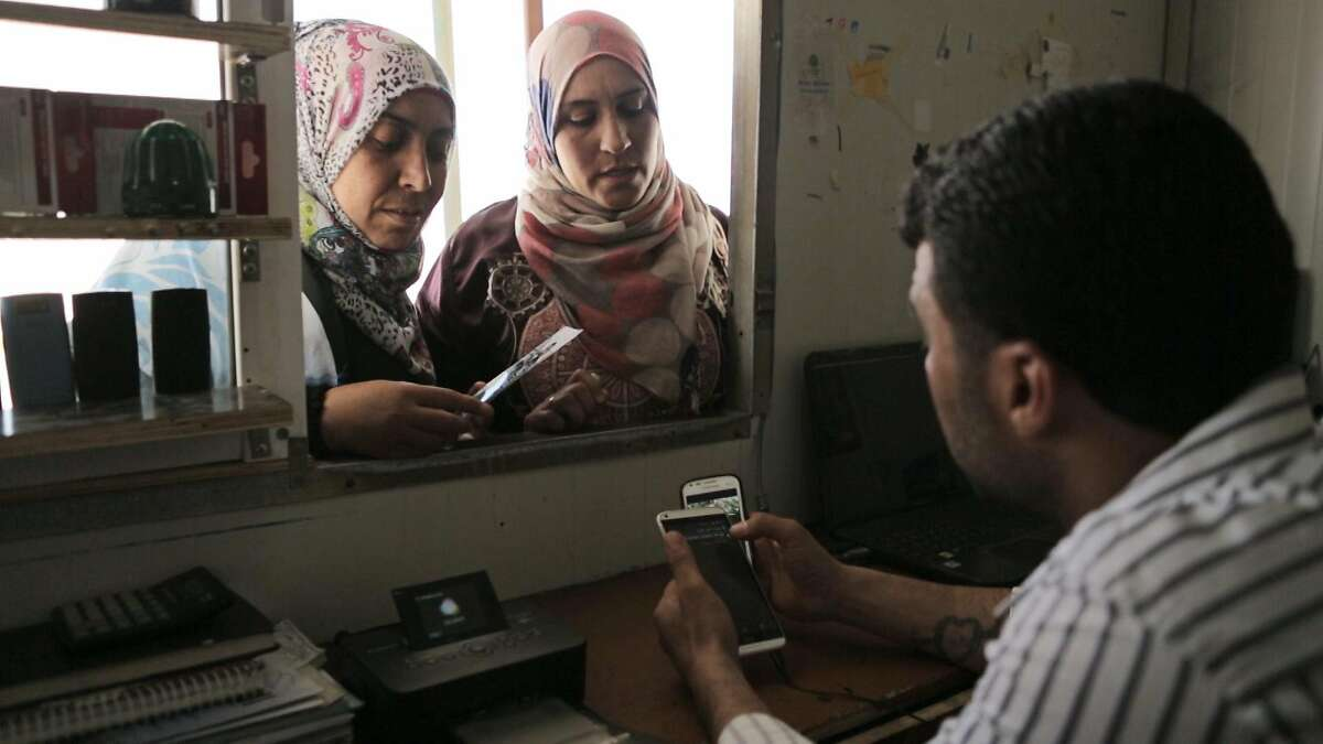 """Maamun helps customers at his mobile repair shop in a Syrian refugee camp in Jordan in the documentary �District Zero."""""""