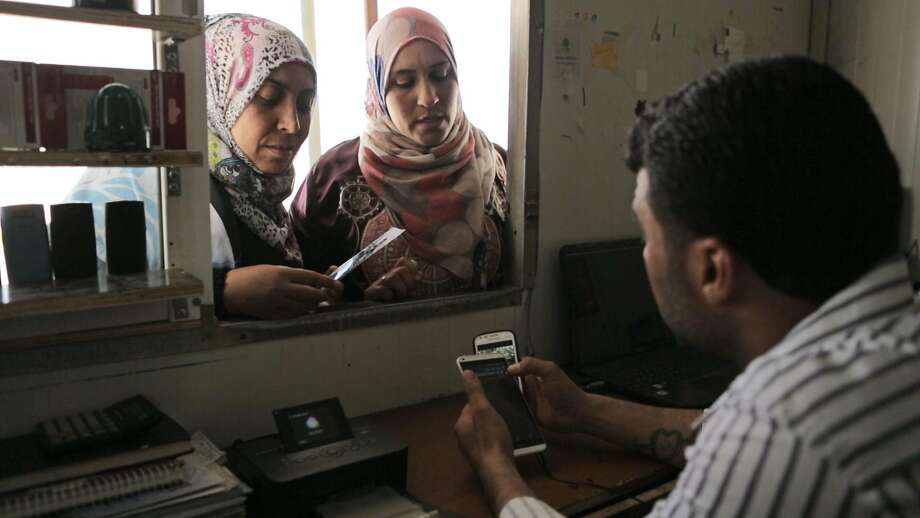 """In Pablo Iraburu's feature-length documentary """"District Zero,"""" Maamun helps customers at his phone repair shop in a Syrian refugee camp in Jordan. Photo: S.F. Frozen Film Festival"""