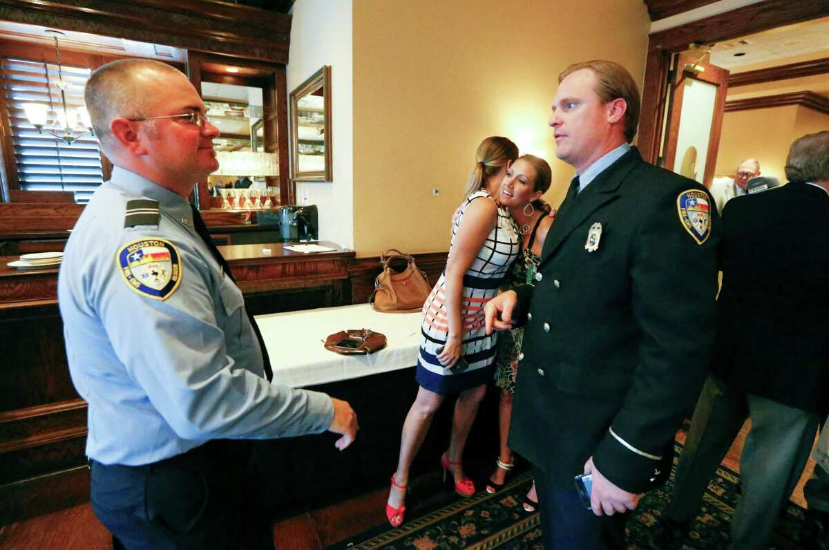 Houston Firefighter Engineer Operator Eric Ruple (left) and Firefighter Patrick Lancton congratulate each other after winning the Independent Insurance Agents of Houston (IIAH), Firefighter of the Year Award Thursday, July 14, 2016, in Houston. Their wives are hugging in the background. This was the 38th year IIAH has worked in conjunction with HFD to recognize the commitment of firefighters and paramedics who have gone far above the call of duty when emergency situations arise.