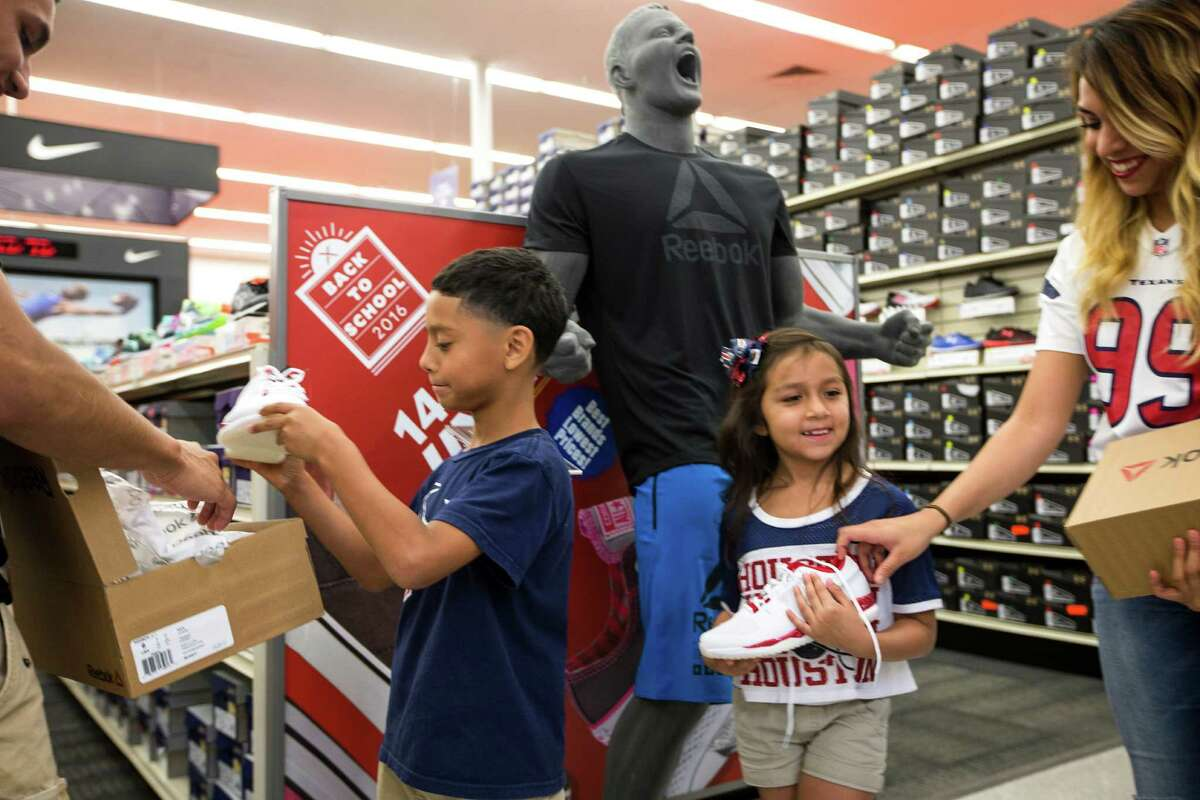 Joshua Banda, left, and Daisy Ortiz pose for a photo in front of a JJ Watt mannequin holding the new Reebok JJI shoe during the launch event for the at the Academy in the 2400 block of the Southwest Freeway on Friday, July 15, 2016, in Houston.