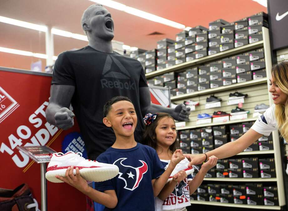 Joshua Banda, left, and Daisy Ortiz pose for a photo in front of a JJ Watt mannequin holding the new Reebok JJI shoe during the launch event for the at the Academy in the 2400 block of the Southwest Freeway on Friday, July 15, 2016, in Houston. Photo: Brett Coomer, Houston Chronicle / © 2016 Houston Chronicle