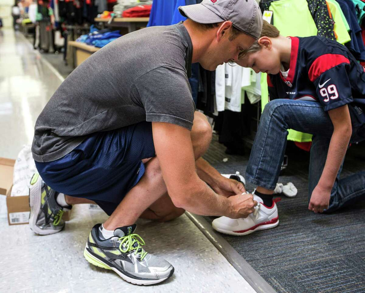 Chad Blaha, left, helps Travis Blaha try on a pair of Reebok JJI during the launch event for the new Reebok shoe at the Academy in the 2400 block of the Southwest Freeway on Friday, July 15, 2016, in Houston.