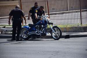 San Antonio Police Department officers clear the scene of a two-vehicle crash involving a motorcyclist, who was hospitalized, and a sedan in the 1300 block of Pleasanton Road on July 15, 2016.