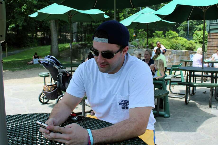 """Mike Keshin plays """"Pokemon Go"""" at the Apple Cart in Mead Park in New Canaan on Tuesday. Photo: Justin Papp / Hearst Connecticut Media / New Canaan News"""