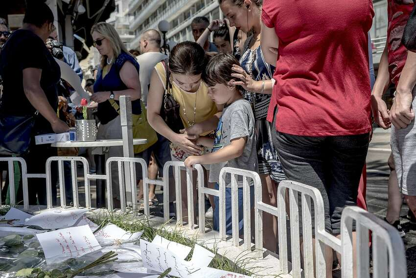 A boy is comforted as people stand around a makeshift memorial near the Promenade des Anglais where a truck barreled for more than a mile through a crowd watching Bastille Day fireworks the night before, in Nice, France, July 15, 2016. The death toll from the terrorist attack rose to 84 on Friday, as the government raced to establish the attacker�s identity, extended a national state of emergency and absorbed the shock of a third major terrorist attack in 19 months. (Andrew Testa/The New York Times)