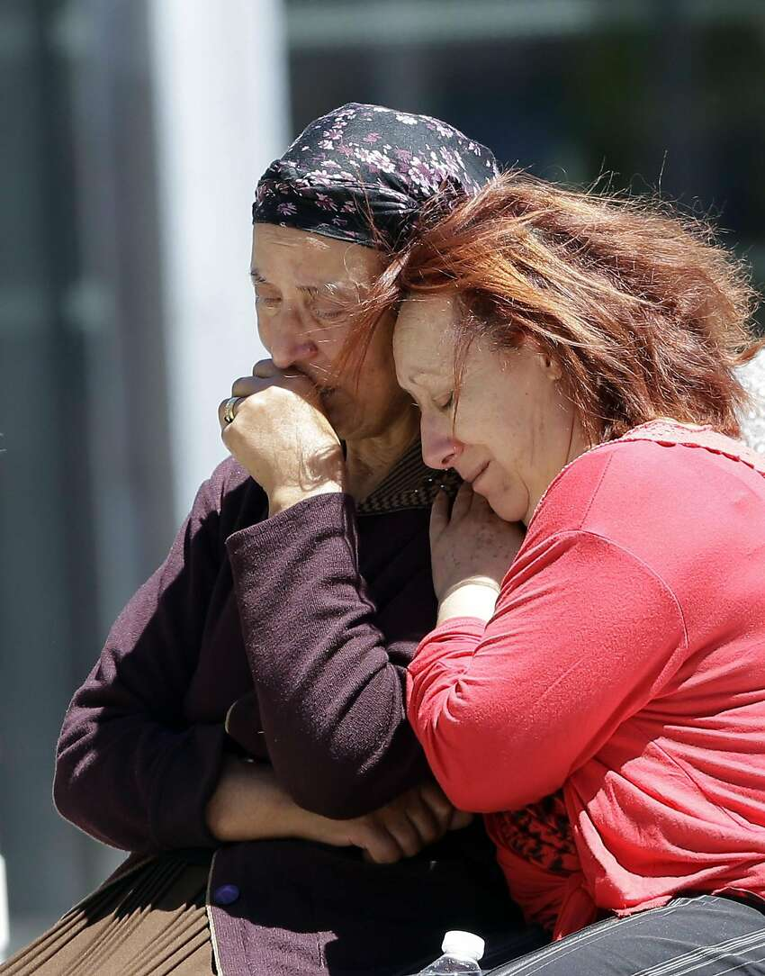 Relatives of the victims of the Bastille Day attack confort each other as they gather in front of Pasteur Hospital in Nice, southern France, Friday, July 15, 2016. A large truck mowed through revelers gathered for Bastille Day fireworks in Nice, killing more than 80 people and sending people fleeing into the sea as it bore down for more than a mile along the Riviera city's famed waterfront promenade. (AP Photo/Claude Paris)