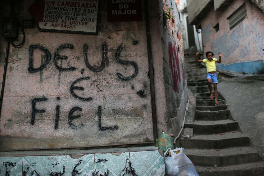 Graffiti reads 'God is Faithful' in the Mangueira 'favela' community on July 11, 2016 in Rio de Janeiro, Brazil. Much of the Mangueira favela community sits about a kilometer away from Maracana stadium, which will be the site of the opening and closing ceremonies for the Rio 2016 Olympic Games. The stadium has received hundreds of millions of dollars in renovations ahead of the World Cup and Olympics. The Morar Carioca plan to urbanize Rio's favelas, or unplanned settlements, by 2020, was one key social legacy project heralded ahead of the Rio 2016 Olympic Games. The plan has mostly failed to materialize. Around 1.4 million residents, or approximately 22 percent of Rio's population, reside in favelas which often lack proper sanitation, health care, education and security due to gang and police violence.
