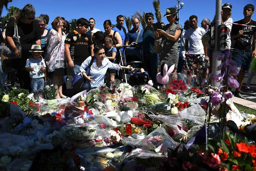 TOPSHOT - People lay flowers in the street of Nice to pay tribute to the victims the day after a gunman smashed a truck into a crowd of revellers celebrating Bastille Day, killing at least 84 people, on July 15, 2016. A Tunisian-born man zigzagged a truck through a crowd celebrating Bastille Day in the French city of Nice, killing at least 84 and injuring dozens of children in what President Francois Hollande on July 15 called a