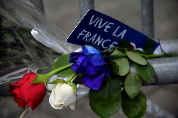 """TOPSHOT - A sign reading """"Long live France"""" is placed near roses in the colors of the French flag at a makeshift memorial in front of the French Embassy in Rome on July 15, 2016, in honour of the victims of an attack in Nice the day before that left at least 84 people dead. A Tunisian-born man zigzagged a truck through a crowd celebrating Bastille Day in the French city of Nice, killing at least 84 and injuring dozens of children in what President Francois Hollande on July 15 called a """"terrorist"""" attack. / AFP PHOTO / TIZIANA FABITIZIANA FABI/AFP/Getty Images"""