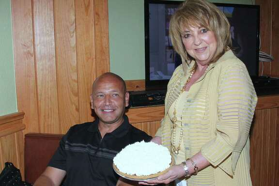 Linda DeWese, owner of Tip Top Cafe, holds a chocolate icebox pie in front of Ed Garza, a former mayor of San Antonio, who claims the pie is his favorite dessert at the restaurant.