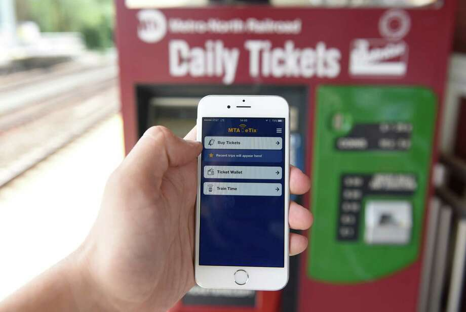 Staff Photographer Tyler Sizemore demonstrates the new MTA eTix mobile app at the Metro-North station in Old Greenwich, Conn. Wednesday, July 13, 2016. MTA eTix is a mobile ticketing app that allows users to purchase Metro-North and Long Island Railroad tickets directly to their mobile devices. eTickets are currently only available to be purchased for Metro-NorthHudson Line and LIRRs Port Washington line, but all remaining lines, including the New Haven line passing through Greenwich, will be active by late August. Photo: Tyler Sizemore / Hearst Connecticut Media / Greenwich Time