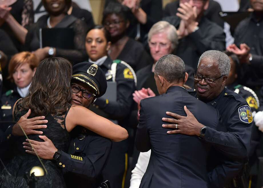 TOPSHOT - First Lady Michelle Obama hugs Dallas Police Chief David Brown (2nd L) as US President Barack Obama hugs Dallas Area Rapid Transit Police Chief James Spiller (R) during an interfaith memorial service for the victims of the Dallas police shooting at the Morton H. Meyerson Symphony Center on July 12, 2016 in Dallas, Texas. President Barack Obama attended a somber memorial Tuesday to five police officers slain in a sniper ambush in Dallas, as he seeks to unify a country divided by race and politics. / AFP PHOTO / MANDEL NGANMANDEL NGAN/AFP/Getty Images Photo: MANDEL NGAN, AFP/Getty Images