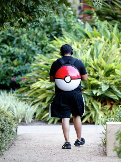 Henry Morales plays Pokemon Go while carrying a Pokeball backpack. Photo: Karen Warren, Houston Chronicle / © 2016 Houston Chronicle