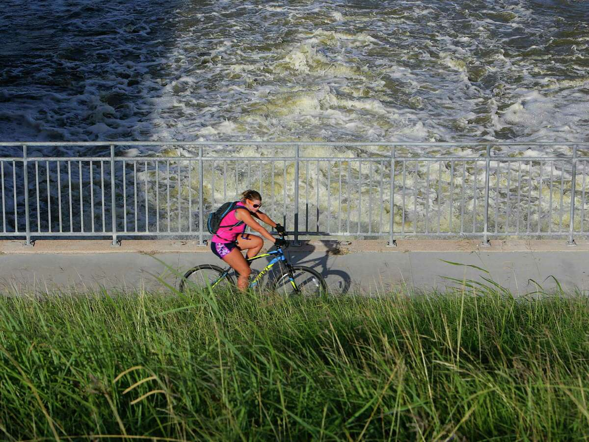 A cyclist passes the outflow where Barker Reservoir empties into the bayou just west of Highway 6, Wednesday, July 6, 2016, in Houston.