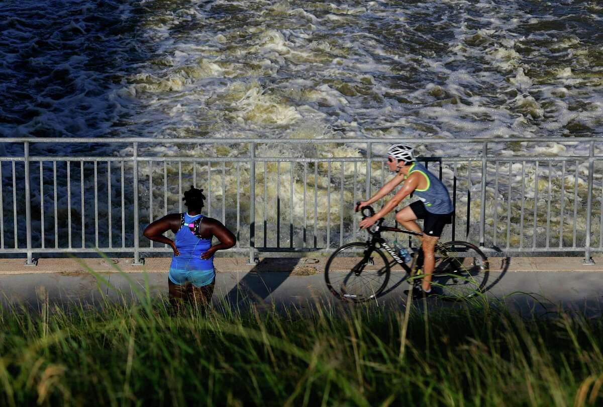 A cyclist and runner pass by the outflow where Barker Reservoir empties into the bayou just west of Highway 6, Wednesday, July 6, 2016, in Houston.