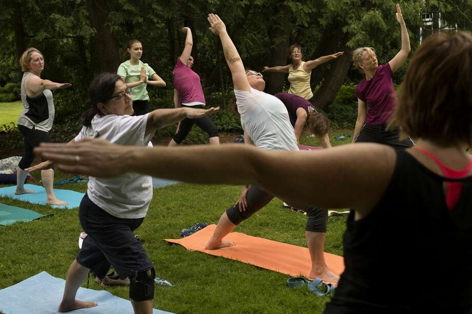 "Yoga class perform different parts of the sun salutation at Dow Gardens on Thursday evening. Fitness and wellness coach with MidMichigan Health, Judi Powers, leads the Tuesday and Thursday evening classes that take place in different locations in Dow Gardens throughout the summer. ""Listen to your body,"" Powers said during the class. ""Do the movements that you're comfortable with."" Photo: Brittney Lohmiller/Midland Daily News/Brittney Lohmiller"