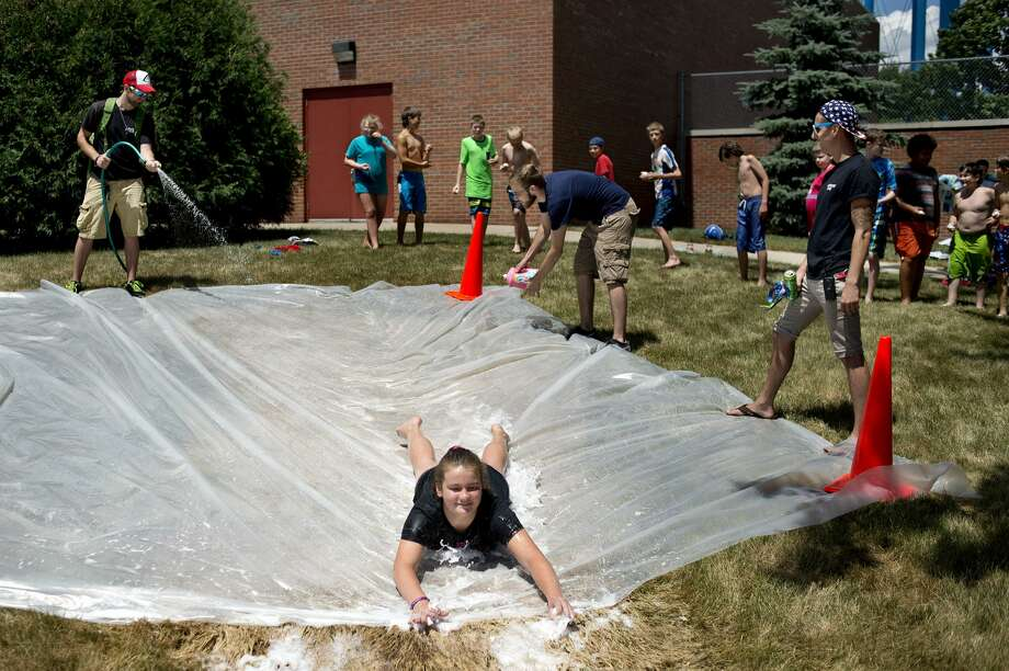"""Twelve-year-old Ashlynn Barnard slides down a sheet of plastics, slippery with water and dish soap, while carrying a """"dragon"""" egg at the Greater Midland Community Center on Thursday afternoon. Barnard and 24 other kids participated in a week long wizard-themed program through The ROCK Center For Youth Development Edge summer adventure series. Participants had to find a hidden egg, protect it will while sliding down the plastic, work as a group to put together three puzzles and find the golden snitch, a colored ping pong ball. Photo: Brittney Lohmiller/Midland Daily News/Brittney Lohmiller"""