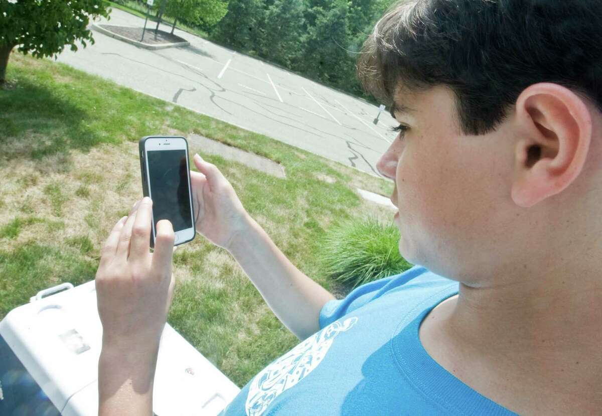 Aaron Melendez, 14 of Danbury, catches Pokemon balls at a station at Walnut Hill Community Church in Bethel which has put out Pokemon Go stations to give out waters and popsicles to people playing the new hit game. Thursday, July 14, 2016