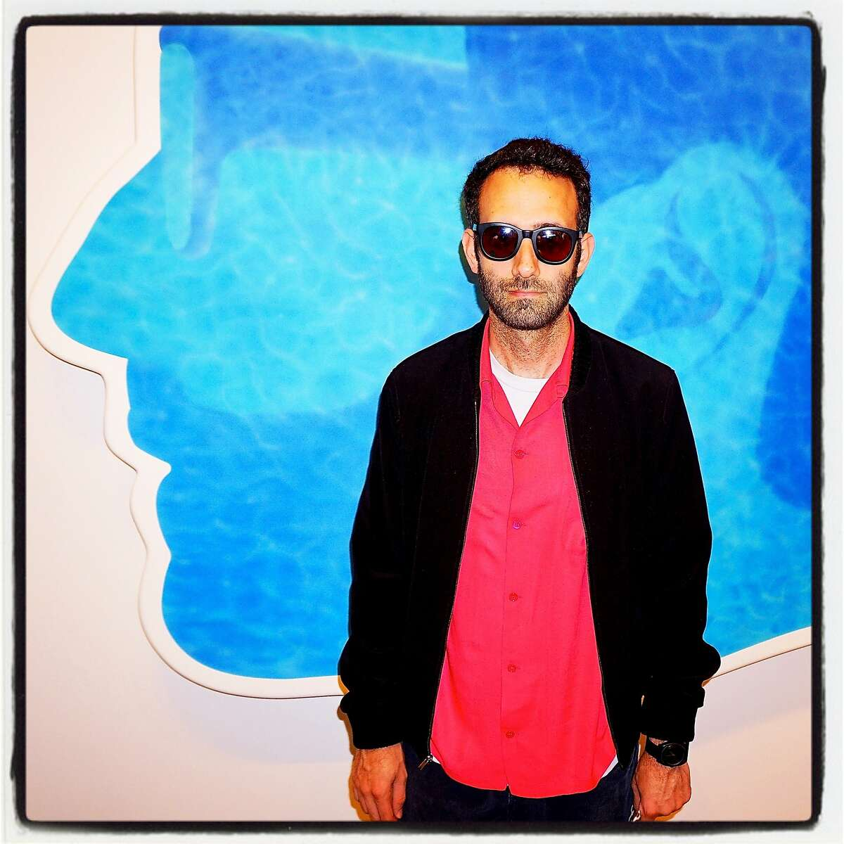 """Artist Alex Israel in front of his work, """"Self Portrait (Swimming Pool) 2014"""" at the Stonescape exhibition. July 2016."""