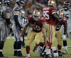 Aaron Lynch (59) celebrates sacking Russell Wilson (3) in the second half of the 49ers game against the Seattle Seahawks at Levi's Stadium in Santa Clara, Calif., on Thursday, October 22, 2015.