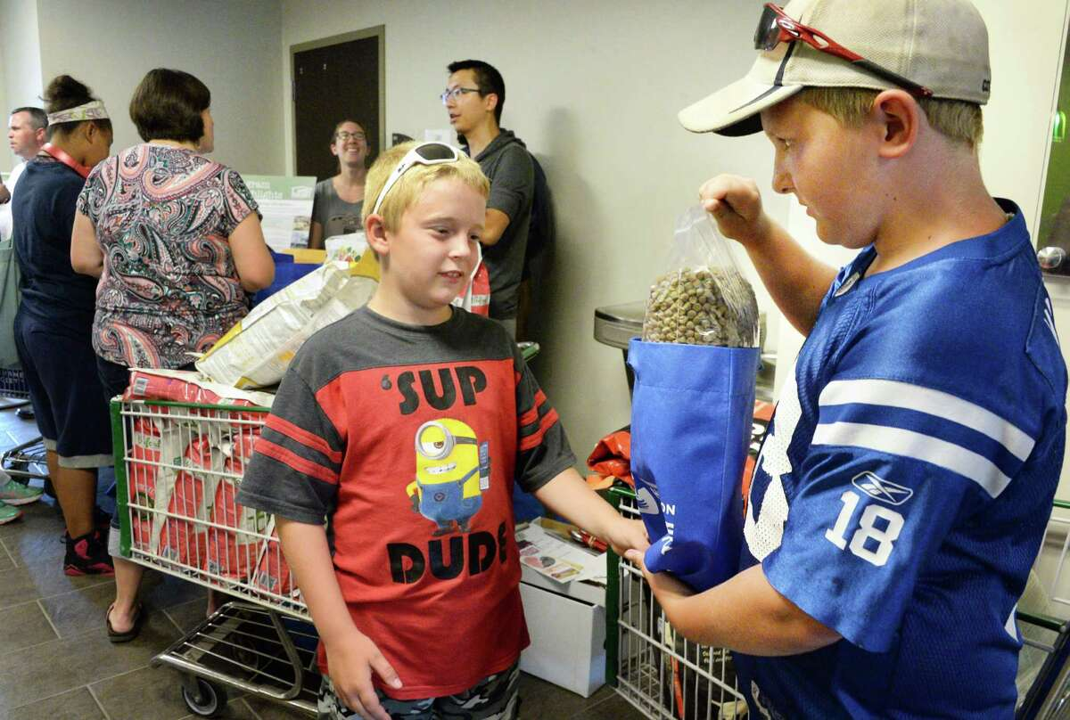 Brothers Dominic, 9, and Dante Congemi, 10, right, of Troy check out free dog food for their Pug Terrier Buddy as Unity House hosts a Pet Food Pantry program by PetFlow and the Mohawk Hudson Humane Society Friday July 15, 2016 in Troy, NY. (John Carl D'Annibale / Times Union)