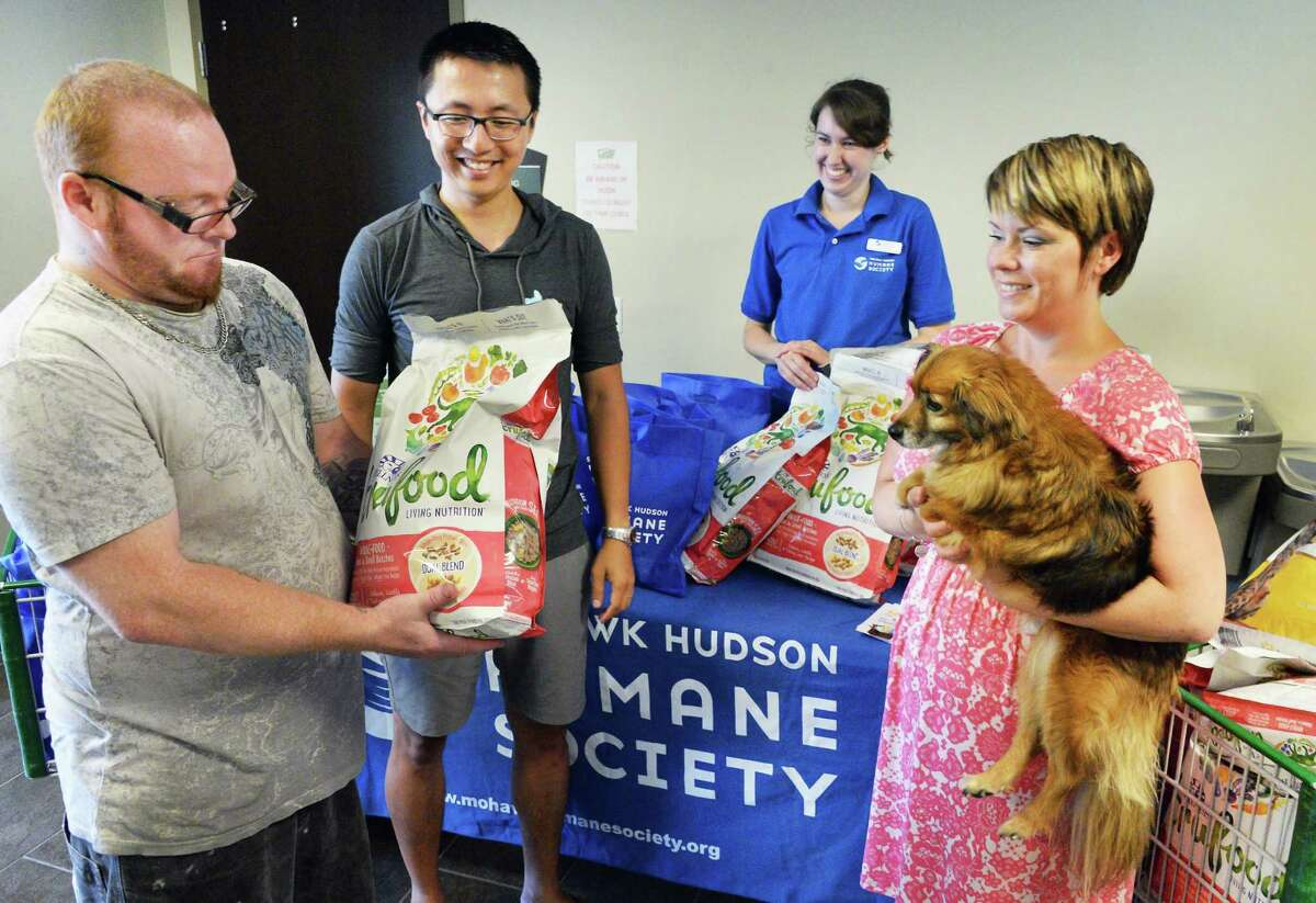 Derrick Harrington, left, of Troy receives free cat food for for his cat Coco from Lei Zhao of PetFlow, Mohawk Hudson Humane Society;s Caitlin Davis and Unity House's Michelle Nadeau and volunteer therapy dog Kingston as Unity House hosts a Pet Food Pantry program by PetFlow and the Mohawk Hudson Humane Society Friday July 15, 2016 in Troy, NY. (John Carl D'Annibale / Times Union)
