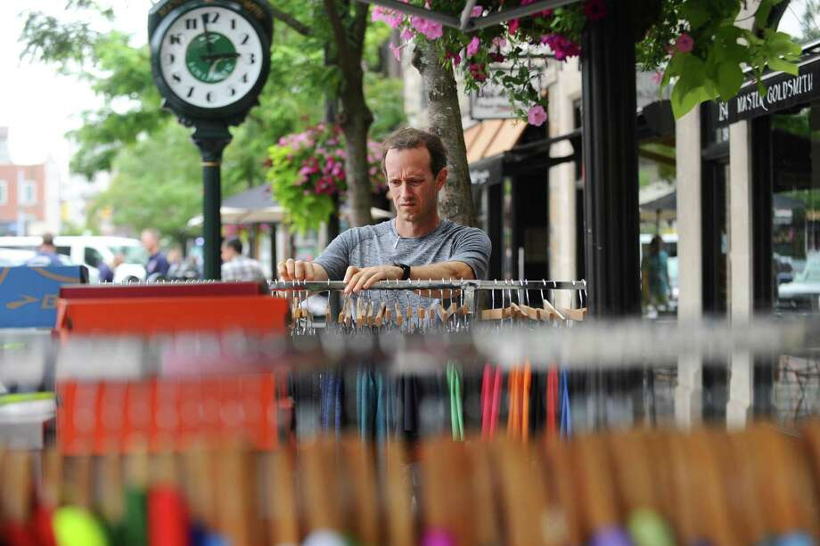 Troy Burk, owner of Fleet Feet Sports on Bedford Street, organizes a rack of clothes during the first day of the Downtown Sidewalk Sales Weekend on Friday. Photo: Michael Cummo / Hearst Connecticut Media / Stamford Advocate