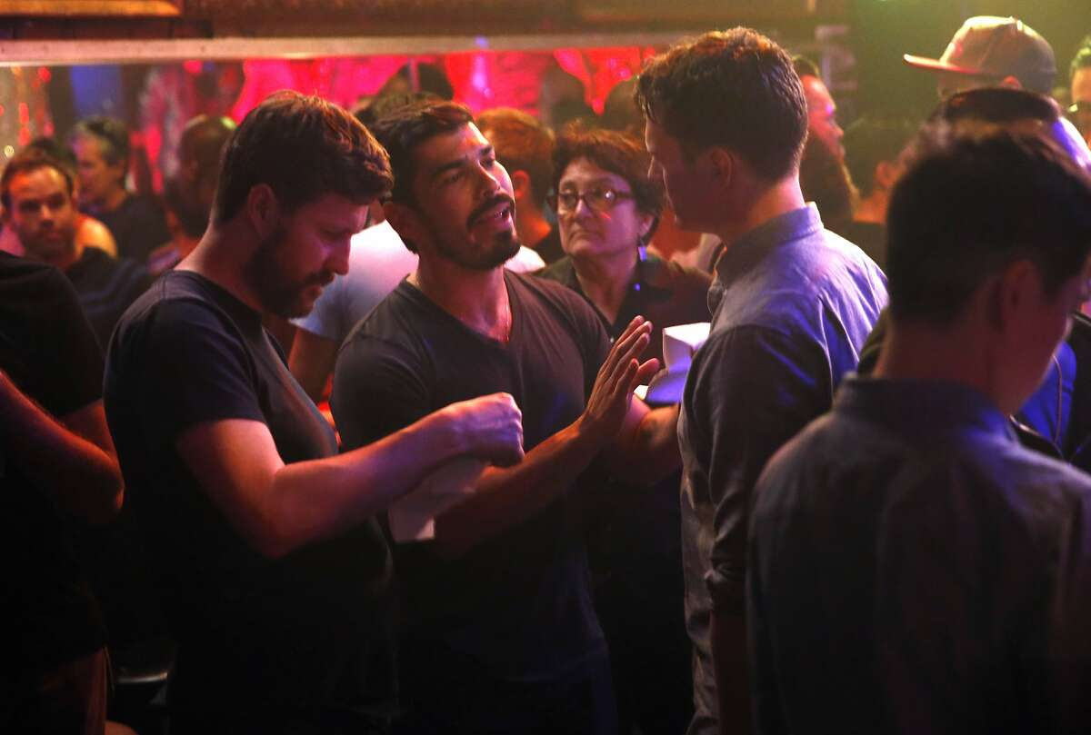 """HBO's """"Looking"""" Raul Castillo rehearses with Jonathan Groff as executive producer/director Andrew Haigh looks at the script as the show films at The Stud Bar in San Francisco, Calif., on Thursday, November 12, 2015."""
