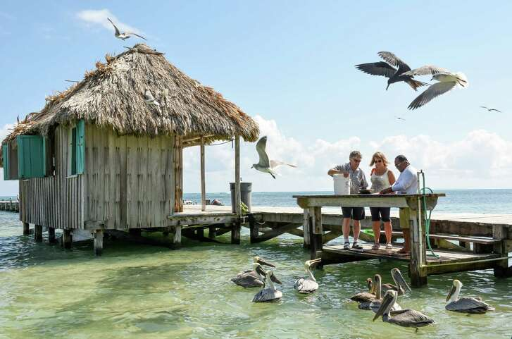 Anglers clean the morning's catch on the boat dock at Victoria House resort outside San Pedro, Belize.