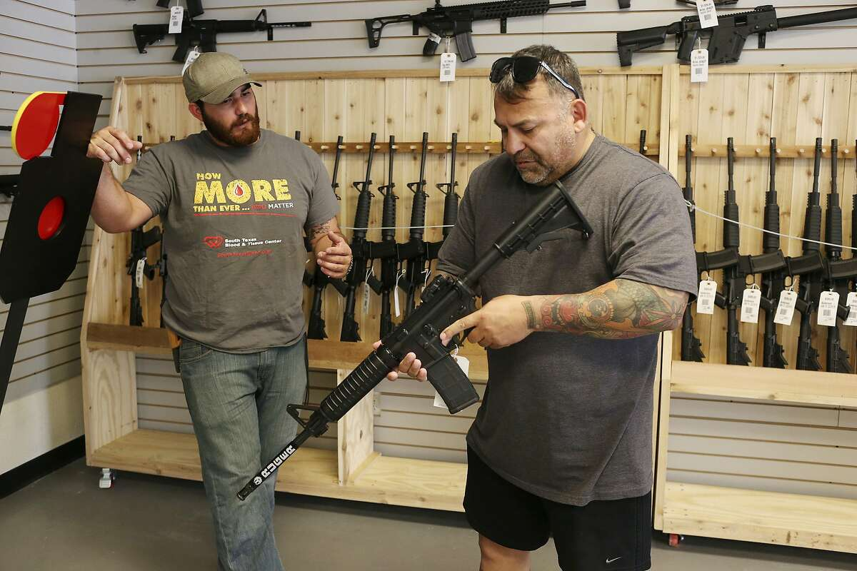 Zeke Hernandez, left, helps out customer, Ifrain Zavala, as he takes a look at an AR-15 at Adelbridge & Company Firearms, Thursday, July 14, 2016.