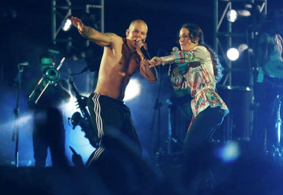 Rene Perez, left, of Puerto Rico's band Calle 13, sings with his sister Ileana Cabra, during a concert in Lago Agrio, Ecuador. Photo: Dolores Ochoa, Associated Press / AP
