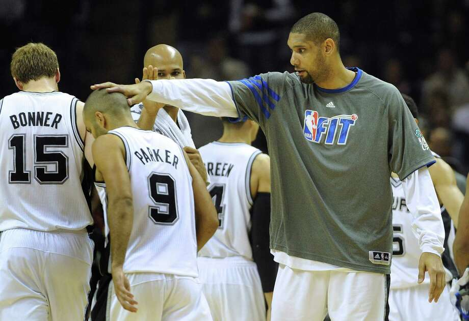 Tim Duncan of the Spurs greets teammate Tony Parker with a pat on the head during a timeout of their game against the New Orleans Hornets at the AT&T Center on Feb. 2, 2012. Photo: Billy Calzada /San Antonio Express-News / San Antonio Express-News