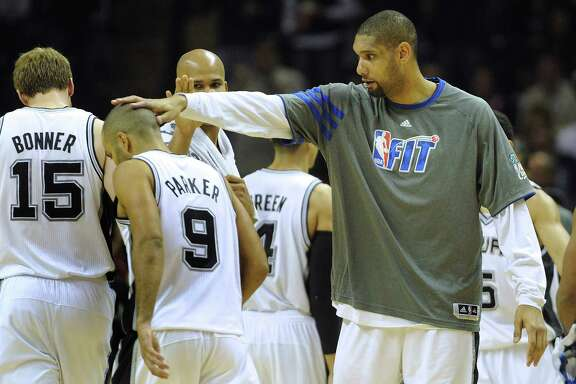 Tim Duncan of the Spurs greets teammate Tony Parker with a pat on the head during a timeout of their game against the New Orleans Hornets at the AT&T Center on Feb. 2, 2012.