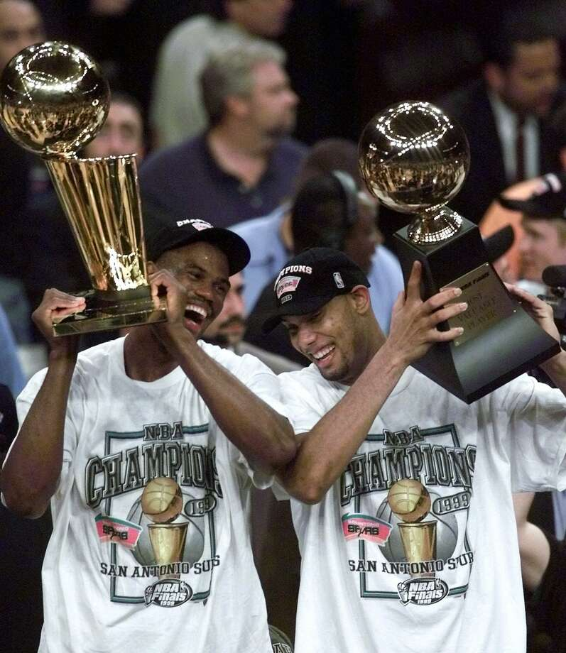 The San Antonio Spurs' David Robinson, left, holds the NBA championship trophy as teammate Tim Duncan holds the Most Valuable Player trophy after defeating the New York Knicks 78-77 in Game 5 of the 1999 NBA Finals on June 25, 1999, at New York's Madison Square Garden. Photo: Mark Lennihan, AP