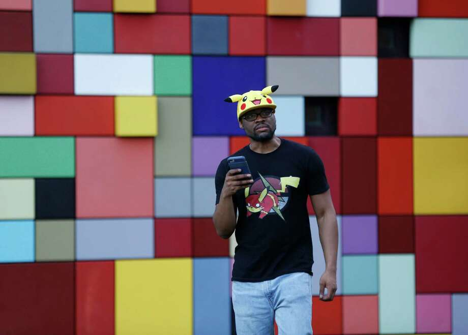 "Michael Simeon, 30, of New Jersey, wears a Pokemon hat and t-shirt while playing Pokemon Go, in Discovery Green, which is a ""gym"", a place where Pokemon players can battle for ownership, Wednesday, July 13, 2016, in Houston. . Gyms attract more players to them, more than other parts of the city, where hundreds have been showing up each night since the Pokeman app started, last week. Photo: Karen Warren, Houston Chronicle / © 2016 Houston Chronicle"