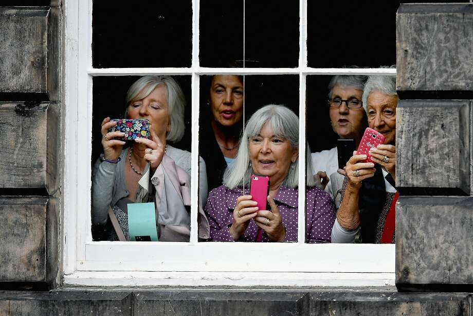 EDINBURGH, SCOTLAND - JULY 15:  Members of the public take pictures from a window as Prime Minister Theresa May, departs Bute House after meeting with First Minister Nicola Sturgeon on July 15, 2016 in Edinburgh, Scotland. Prime Minister flew in for Brexit talks with the First Minister, and were expected to express that she wants the Scottish Government to play a key role in negotiations with the EU.  (Photo by Jeff J Mitchell/Getty Images) Photo: Jeff J Mitchell, Getty Images