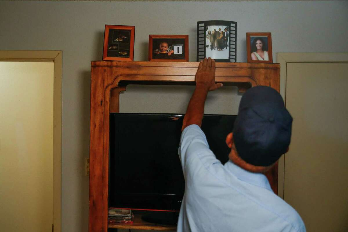 James Giddens looks at pictures of his brother, Rickey Giddens, in his old room Thursday, May 12, 2016 in Missouri City. His brother died after an explosion at the PeroxyChem plant in Pasadena in January.