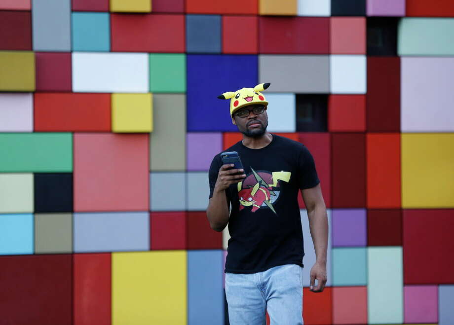 "Michael Simeon, 30, of New Jersey, wears a Pokemon hat and t-shirt while playing Pokemon Go, in Discovery Green, which is a ""gym"", a place where Pokemon players can battle for ownership, Wednesday, July 13, 2016, in Houston.  Gyms attract more players to them, more than other parts of the city, where hundreds have been showing up each night since the Pokeman app started, last week.  ( Karen Warren  / Houston Chronicle ) Photo: Karen Warren, Staff / © 2016 Houston Chronicle"