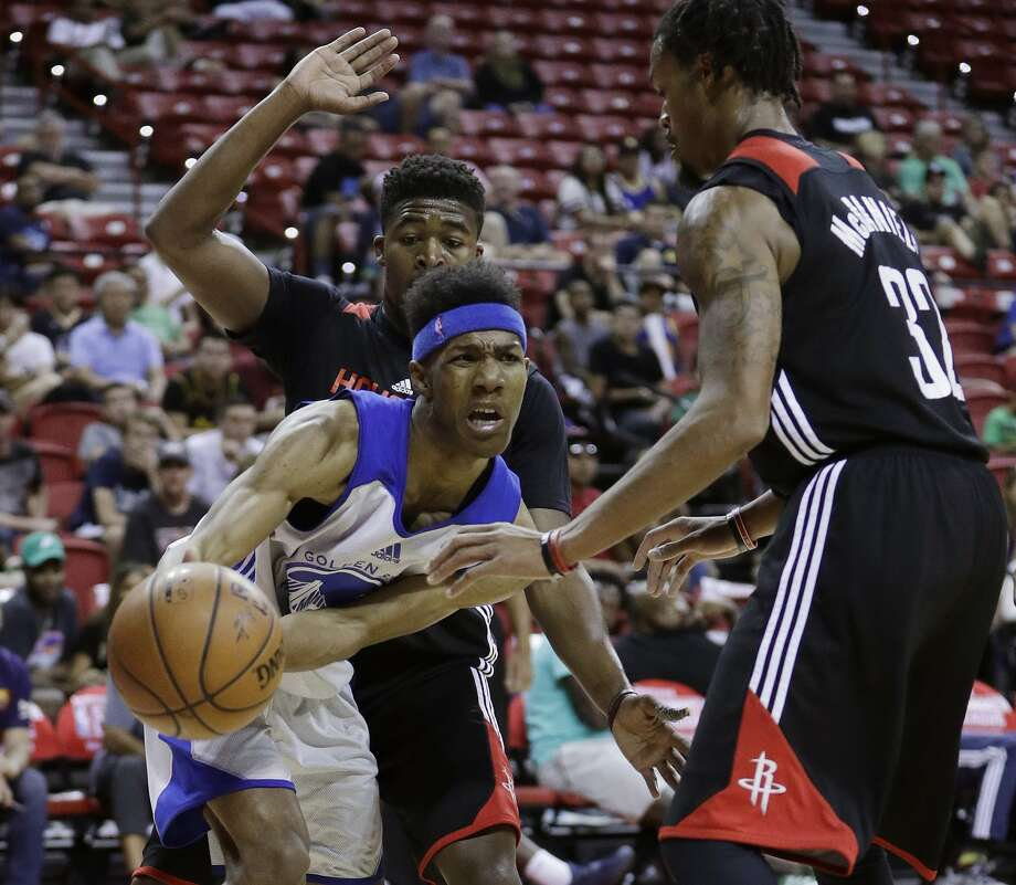 Golden State Warriors' Patrick McCaw passes around Houston Rockets' K.J. McDaniels, right, during the second half of an NBA summer league basketball game July 13, 2016, in Las Vegas.  Photo: John Locher, Associated Press