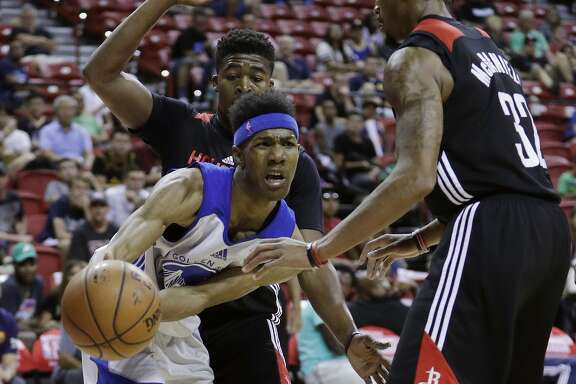 Golden State Warriors' Patrick McCaw passes around Houston Rockets' K.J. McDaniels, right, during the second half of an NBA summer league basketball game, Wednesday, July 13, 2016, in Las Vegas. (AP Photo/John Locher)