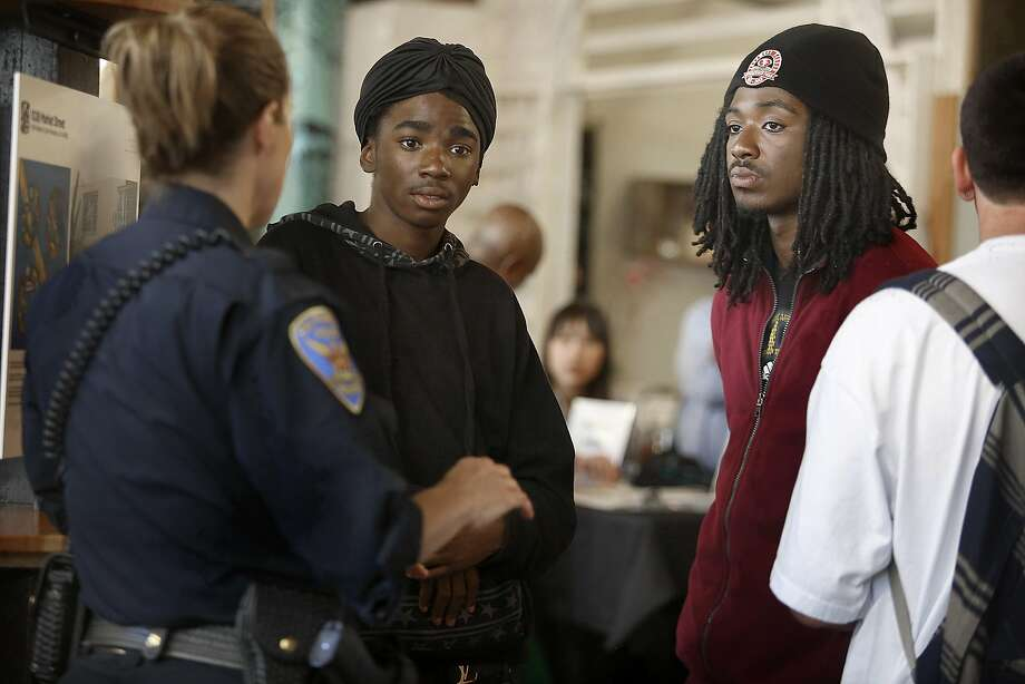 Jayson Christian (center) and Michael Willis talk to Police Capt. Teresa Ewins while attending the job fair to help put Tenderloin residents on track to employment. Photo: Liz Hafalia, The Chronicle