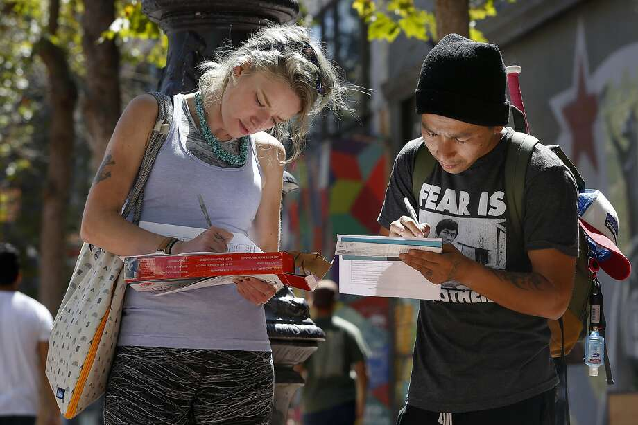 Rennie Bar-Illan (left) and Cuu Tran fill out applications outside during job fair in S.F.'s Tenderloin district. Photo: Liz Hafalia, The Chronicle