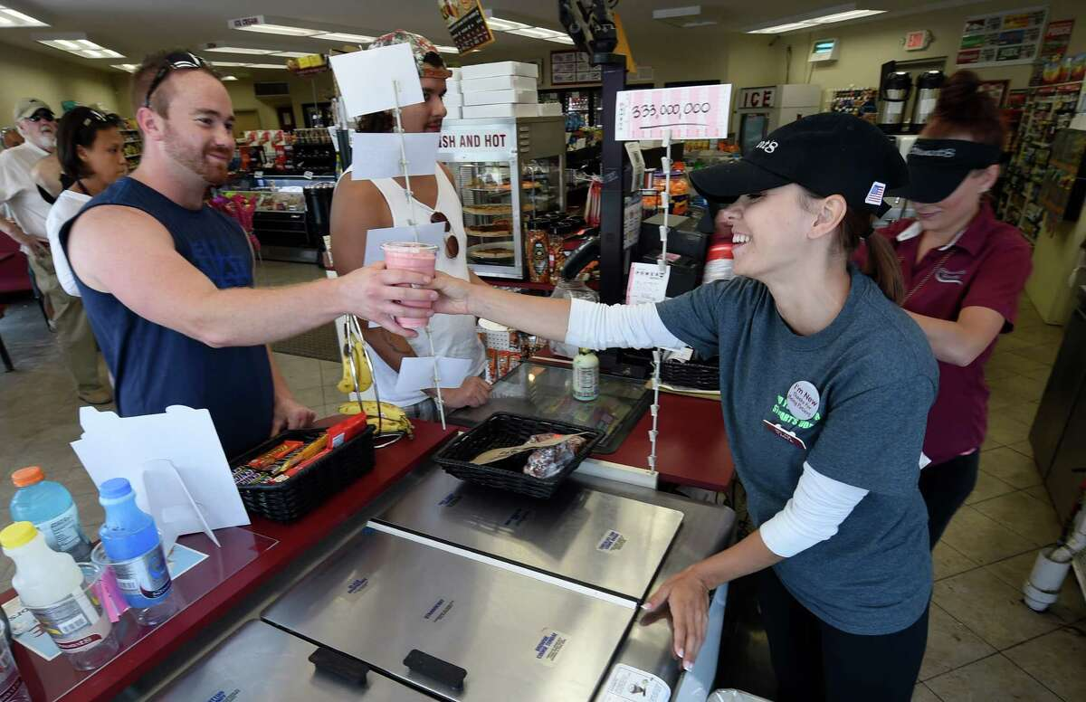 Associate Tanya Schreifel-Snide, right, hands a sherbet cooler to Allan Teller of Clifton Park at the Stewart's on Route 9P Friday July 15 2016 in Stillwater, N.Y. (Skip Dickstein/Times Union)